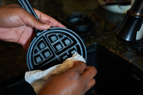 Wiping the Cast Iron Stuffed Waffle Iron with a paper towel