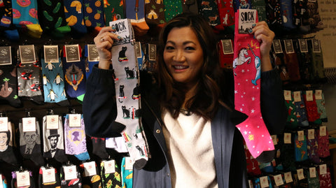 Ji in front of the eclectic sock display at shop Enjoy, An Urban General Store. Brian Rich/Sun-Times