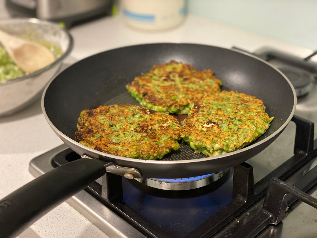 Pea and dill fritters cooking in the pan