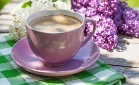 Coffee cup and colorful lilac flowers on garden table_ karandaev
