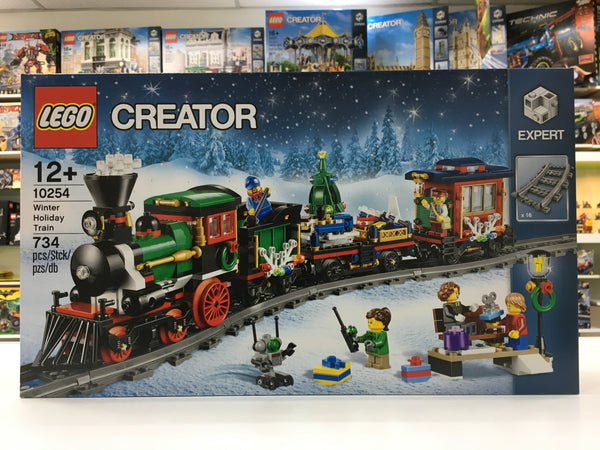 LEGO 10254 Winter Holiday Train - Gather the family for some festive LEGO® building fun with this charming model featuring a full circle of track, boarding platform with bench and lamppost, a Power Functions upgradable train engine with brick-built smoke bellowing from its stack, coal tender, flatbed wagon with a rotating holiday tree, toys and gifts, and a red caboose with a detailed interior and table.