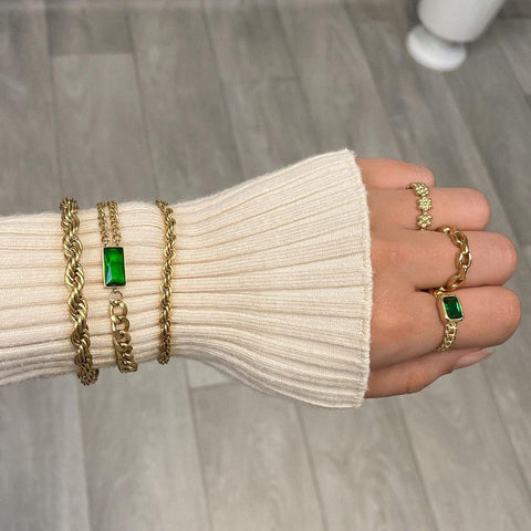Woman's arm wearing a white jump with multiple bracelets and multiple rings being worn