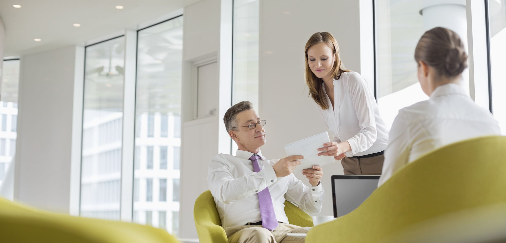 image of a man and two women discussing business