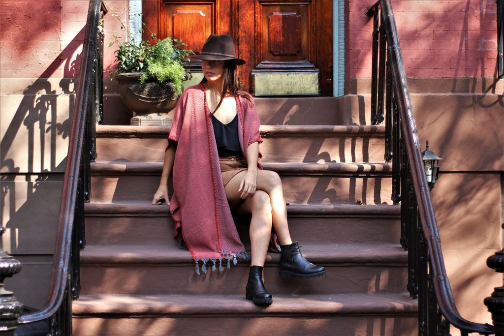 Woman wearing a kaftan sitting on the steps of a Brooklyn brownstone
