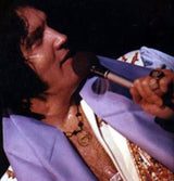 Close of up of Elvis wearing a coin necklace.