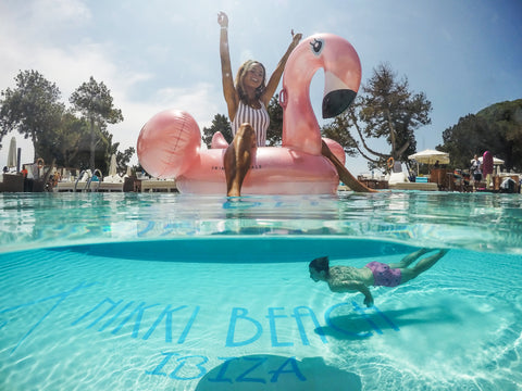 Rose golden flamingo in the pool with someone swimming under it
