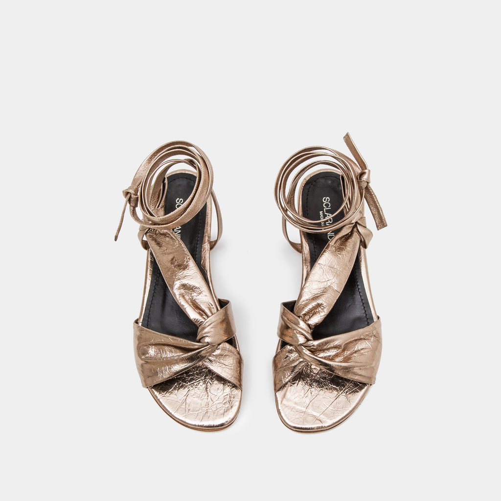 Bronze metallic Knotted nappa flat sandal with an ankle tie wrap