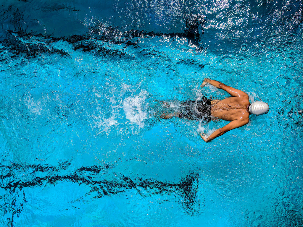 man swimming for sport in an indoor pool