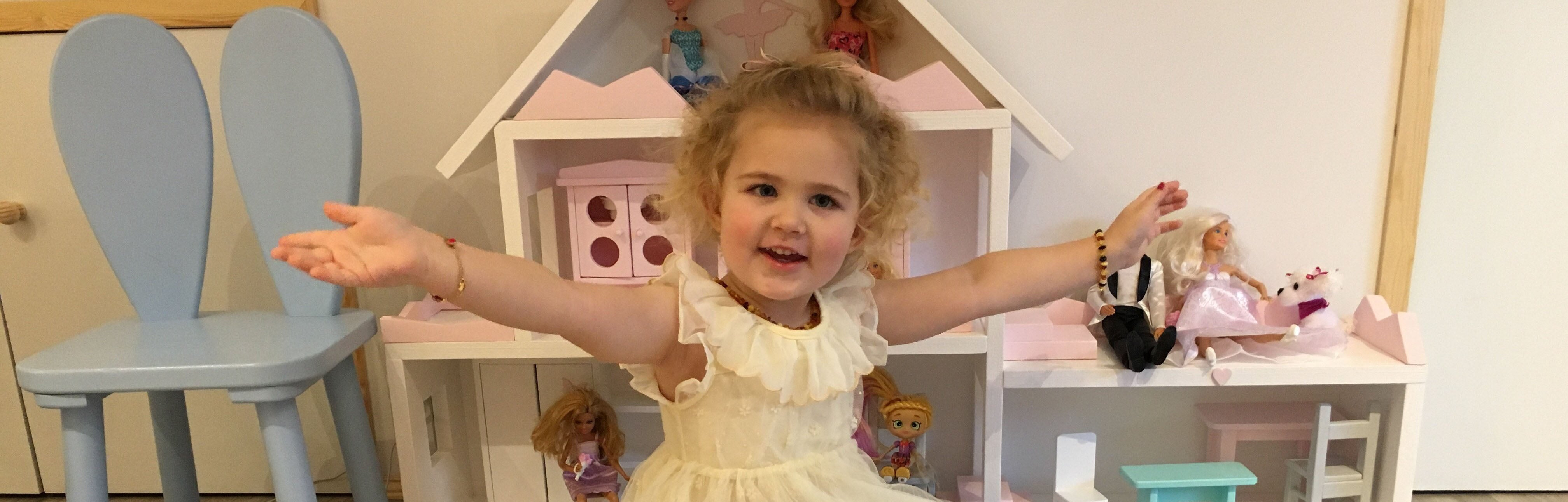 happy girl in front of wooden dolls house