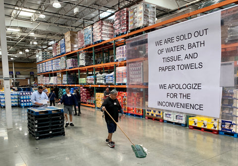 "Coronavirus: Costco store with large sign over shelves saying ""we are sold out of water, bath tissue, and paper towels."""