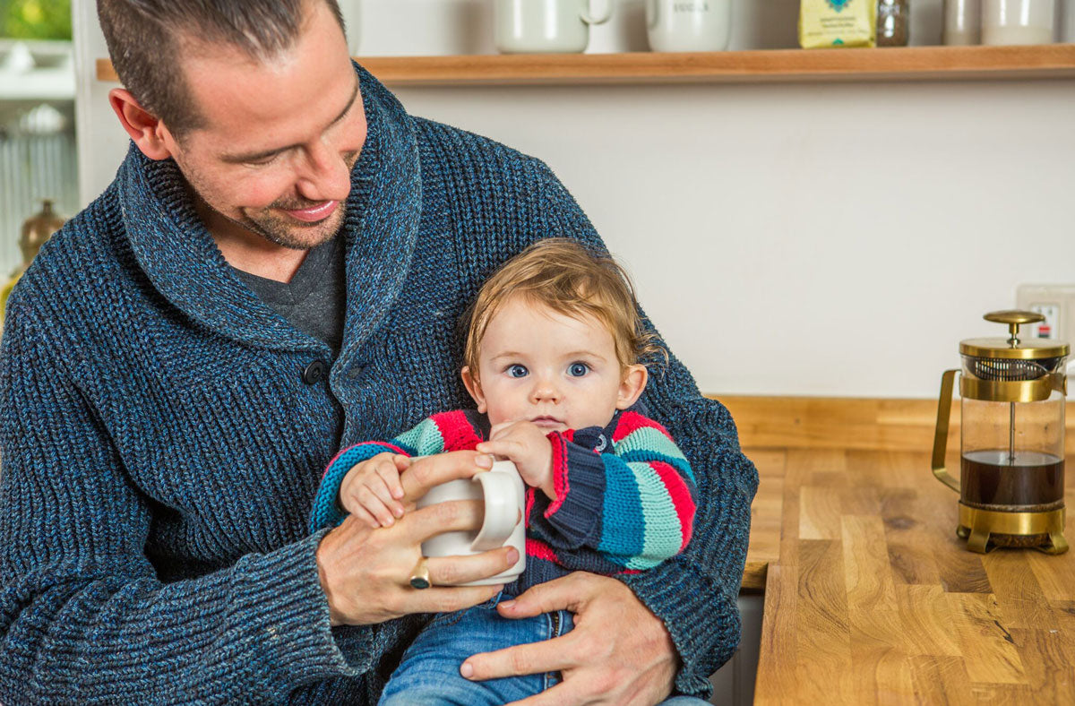 Dad holding child while drinking coffee