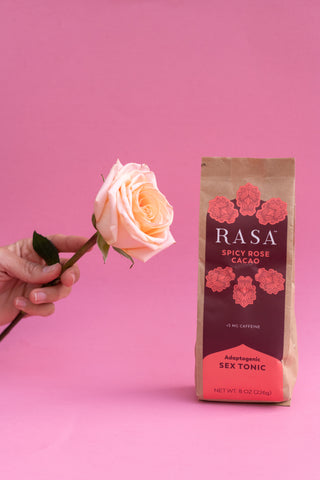 Hand holding rose and bag of Aphrodisiac Spicy Rose Cacao Rasa