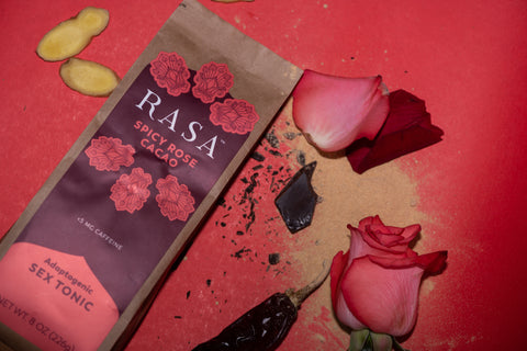 Spicy Rose Aphrodisiac Rasa with Maca powder, rose petals, chocolate, chiles, and ginger slices on red background