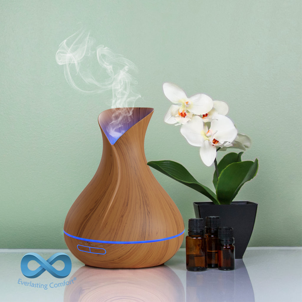 oil diffuser next to a flower on a green background