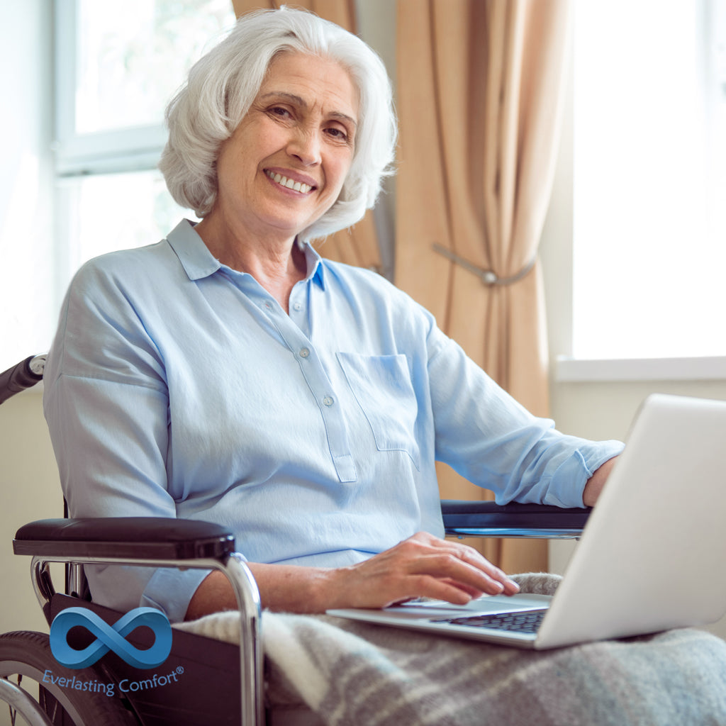 an elderly woman in a wheelchair sits at a computer