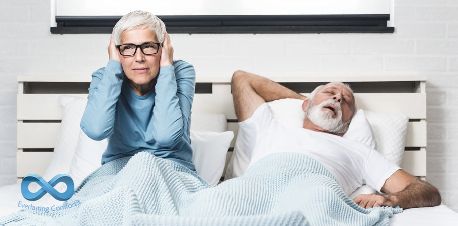 woman covers ears from husband's snoring