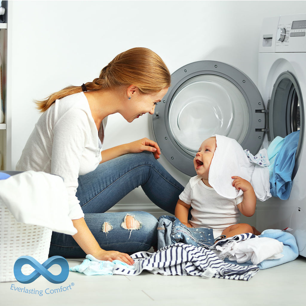 mother and child laugh while sitting near the washing machine