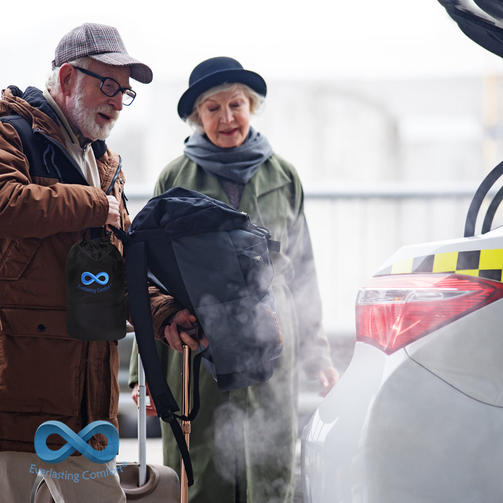 An elderly couple puts things in a taxi trunk