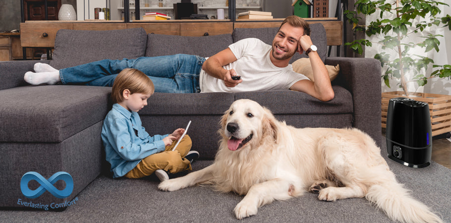 father watches TV on the couch, the child plays on the tablet, the dog sits nearby