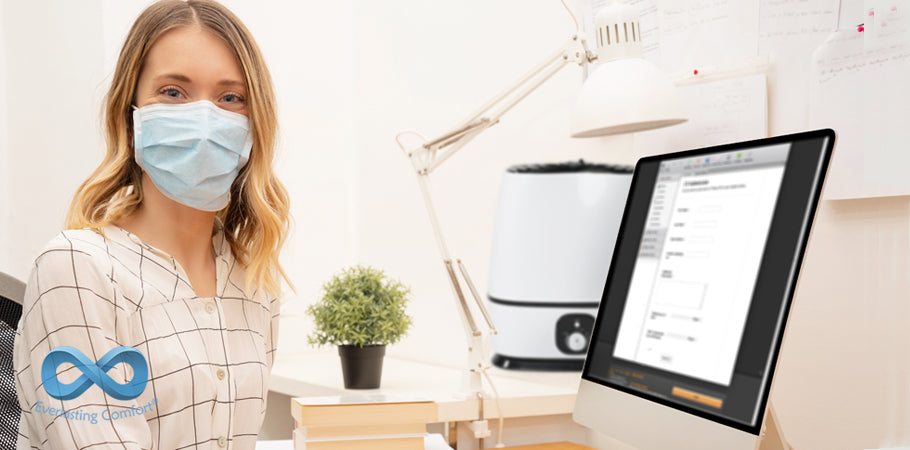 girl in a medical mask sits in front of a computer monitor