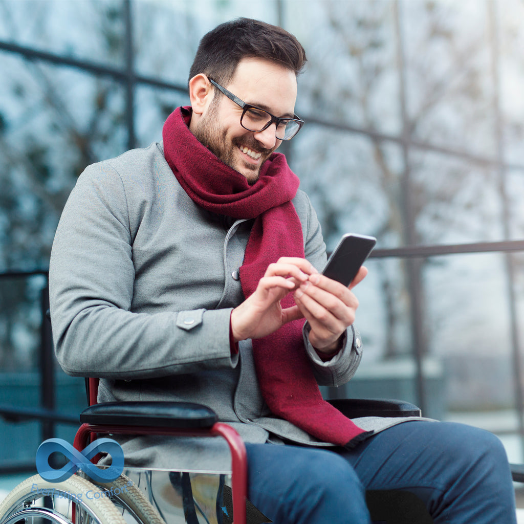 a man in a wheelchair looks at the phone and laughs