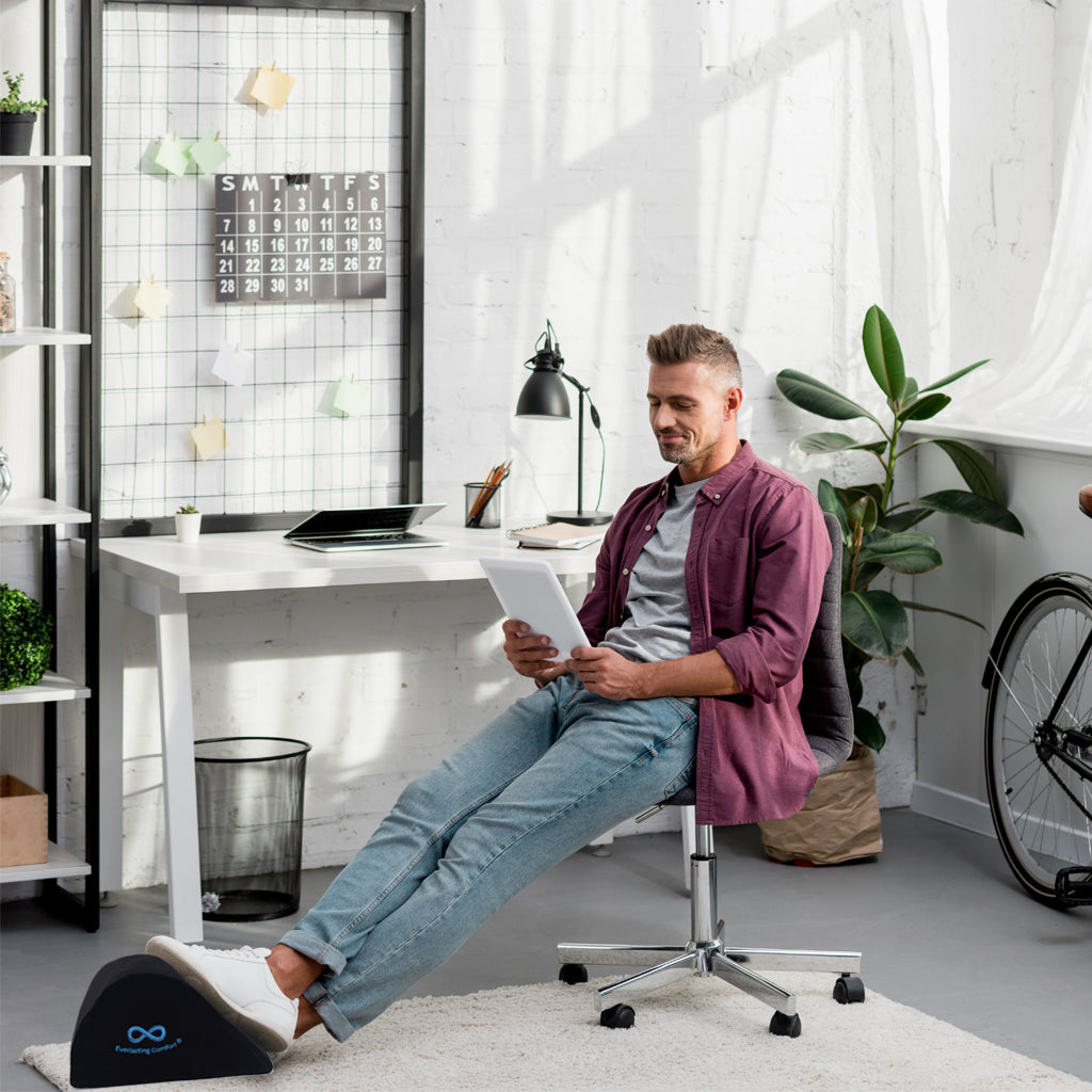 a man looking at a tablet in an office chair