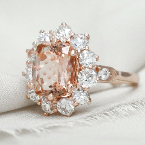 this stunning custom engagement ring has a morganite center stone and old european cut diamond halo