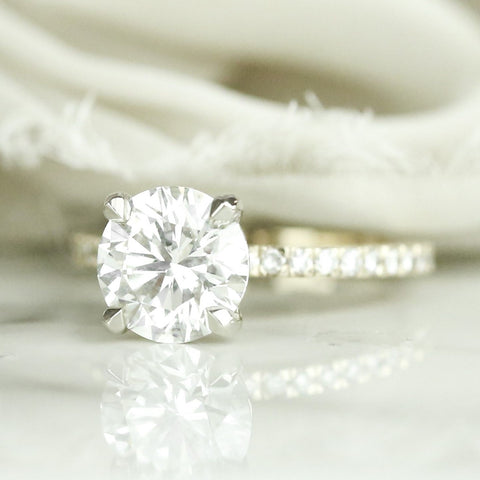 round diamond engagement ring set with four claw prongs and diamonds on the band