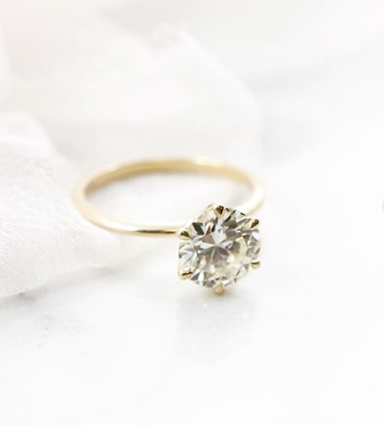 round solitaire diamond engagement ring with a thin yellow gold band