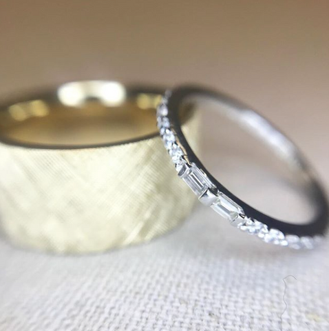 yellow gold chunky men's wedding band with a textured finish and a white gold women's diamond eternity band