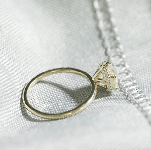 solitaire diamond custom prong set engagement ring with a hidden diamond halo and a thin yellow gold band