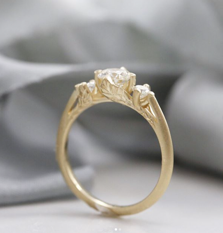 custom diamond engagement ring with leaf details on the side of the yellow gold ring