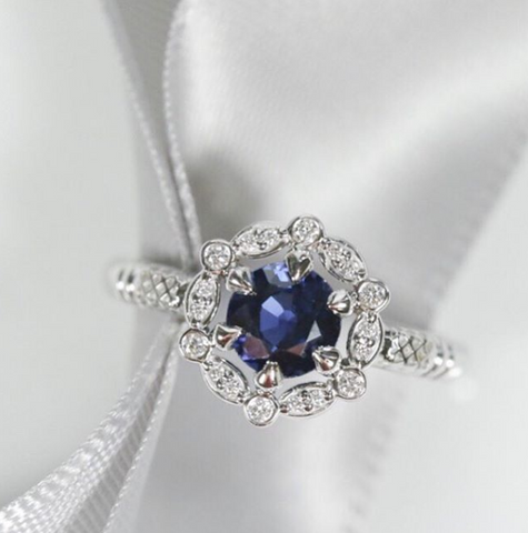 Round blue classic sapphire custom engagement ring with a unique diamond halo set in white gold