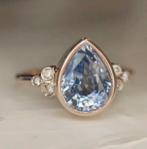 pear shaped pastel blue sapphire bezel set custom engagement rings with three round diamonds on each side