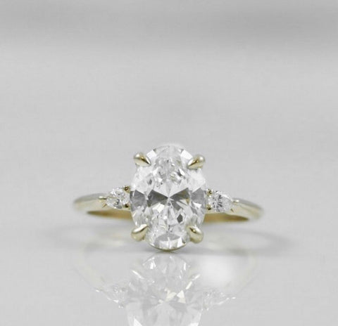 oval diamond engagement ring with yellow gold band and pear shaped side stones