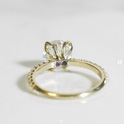 Custom solitaire diamond engagement ring set in yellow gold with two hidden gemstones under the center stone