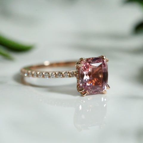 Custom cushion cut pink sapphire and diamond engagement ring set in rose gold with double claw prongs