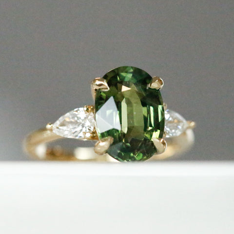 green oval sapphire engagement ring with pear diamond side stones