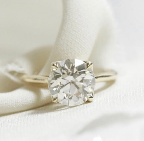 solitaire diamond engagement ring with an old european cut diamond set in 14k yellow gold with claw prongs