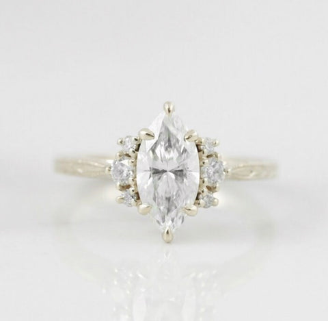 marquise diamond custom engagement ring with three diamonds on each side set in 14k yellow gold with an engraved band