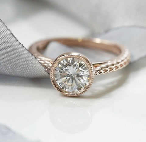 custom bezel set round diamond engagement ring with a milgrain halo and braided band