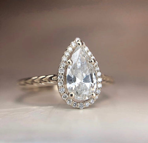 custom pear shaped diamond engagement ring with a delicate diamond halo set in 14k yellow gold with a braided band