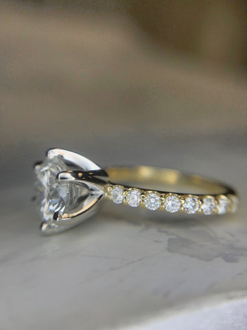 Custom diamond solitaire engagement ring with a yellow gold diamond band