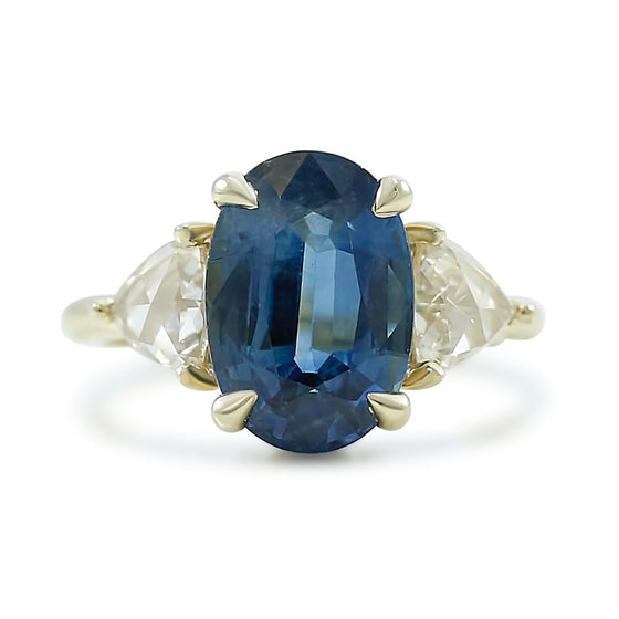 oval prong set sapphire ready to purchase engagement ring with triangle shaped rose cut diamonds on both side of center stone 14k yellow gold