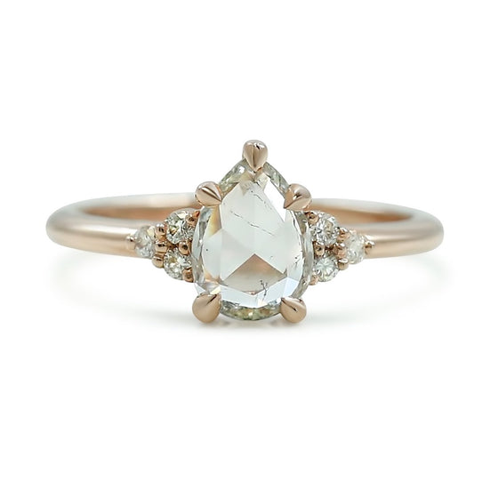 rose cut rose gold pear shaped diamond engagement ring with cluster side stones and a thin rose gold band