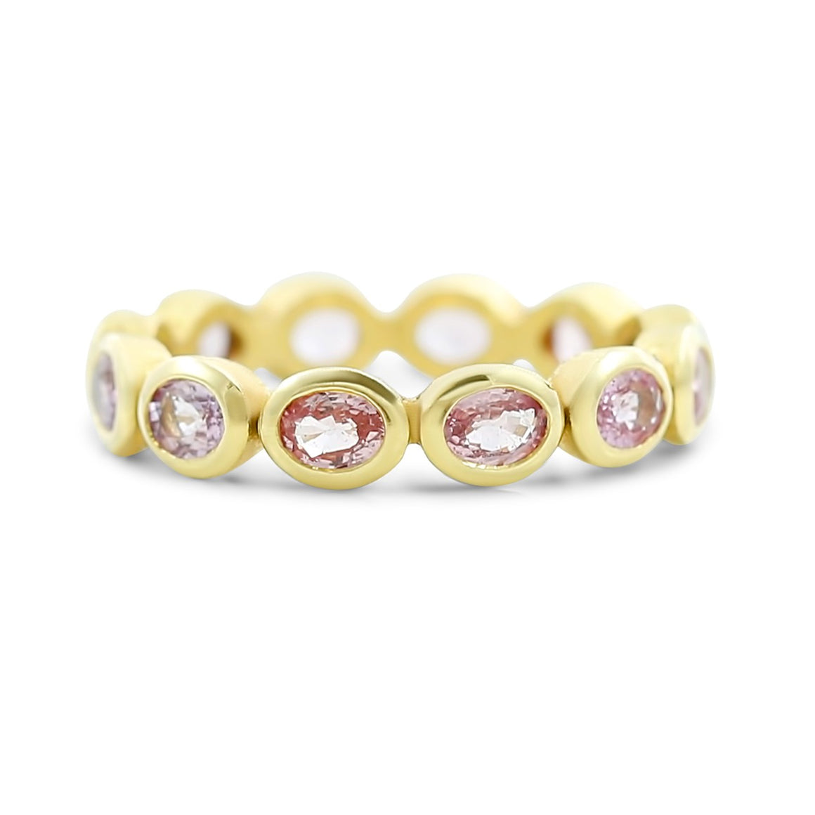 pastel pink sapphire eternity band with bezel set sapphires all the way around the band 18k yellow gold