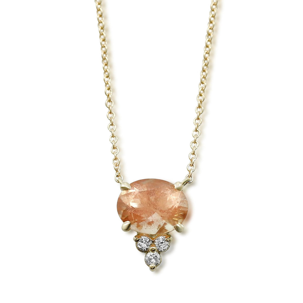 Oregon sunstone necklace with a cluster of round white diamonds underneath gemstone and a yellow gold chain