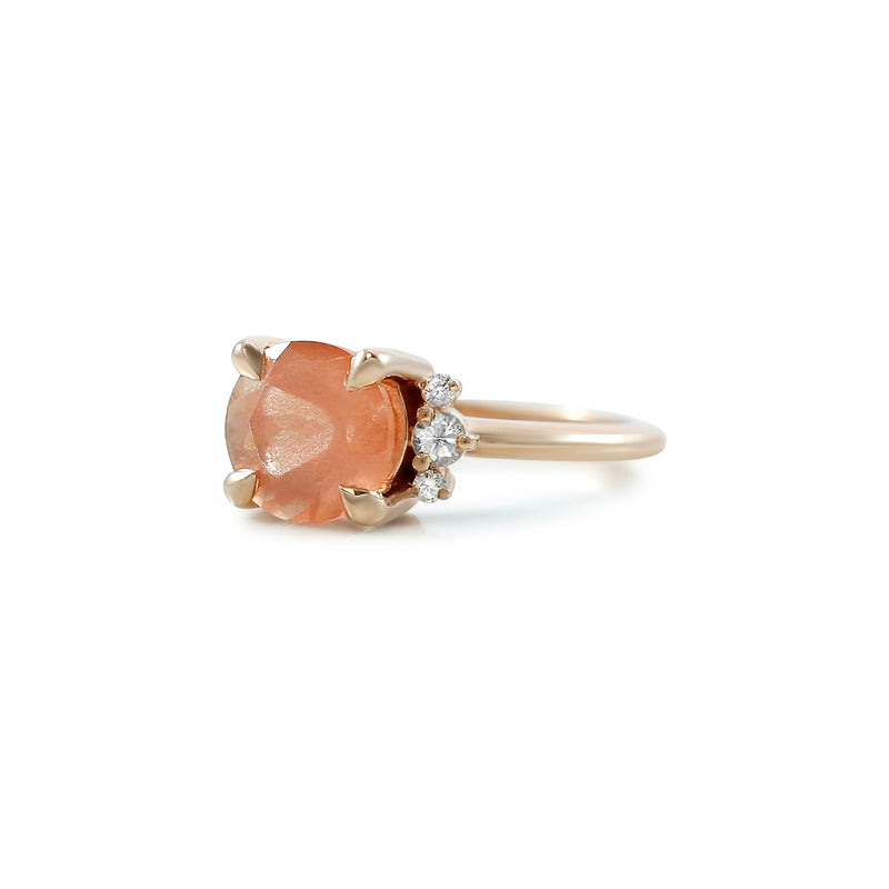 round sunstone and diamond ring prong set in rose gold with a thin simple band