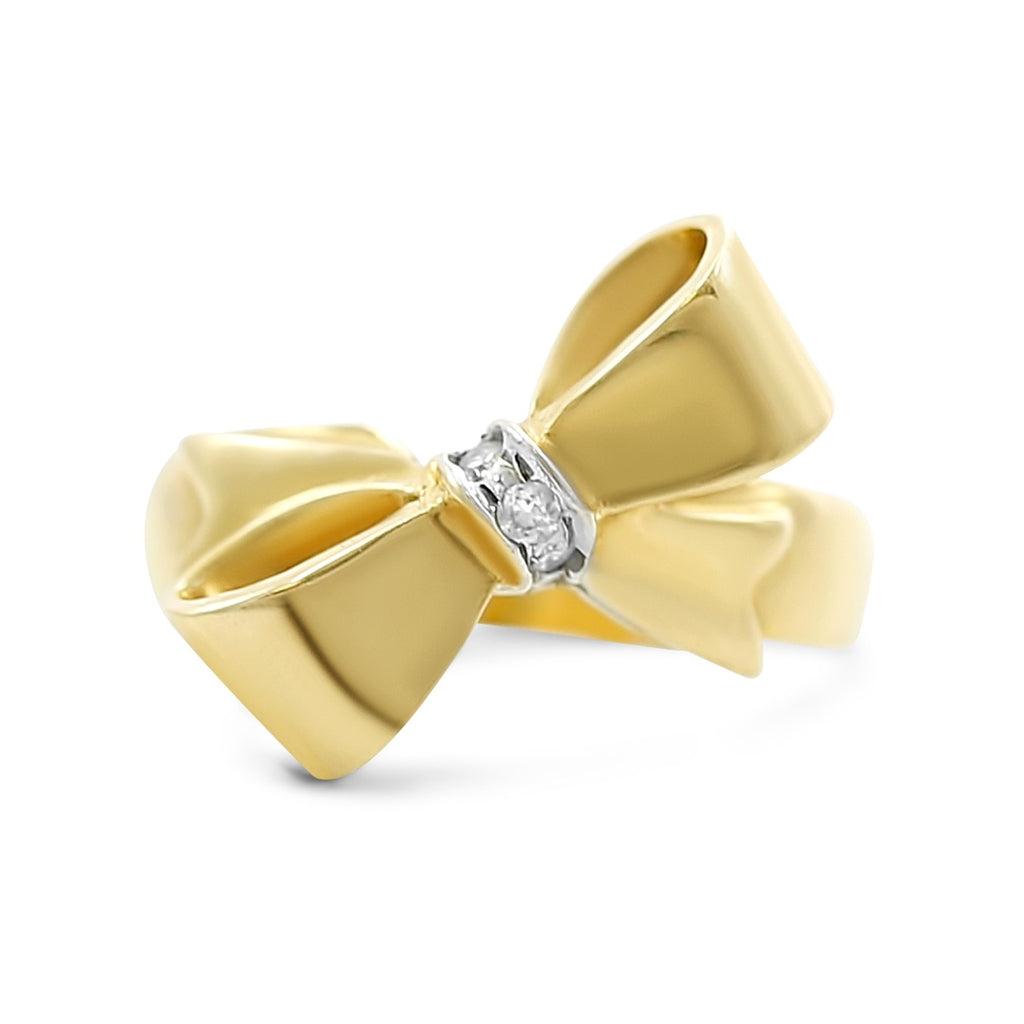 18k yellow gold antique everyday ring with a bow and dainty white diamonds in center of bow