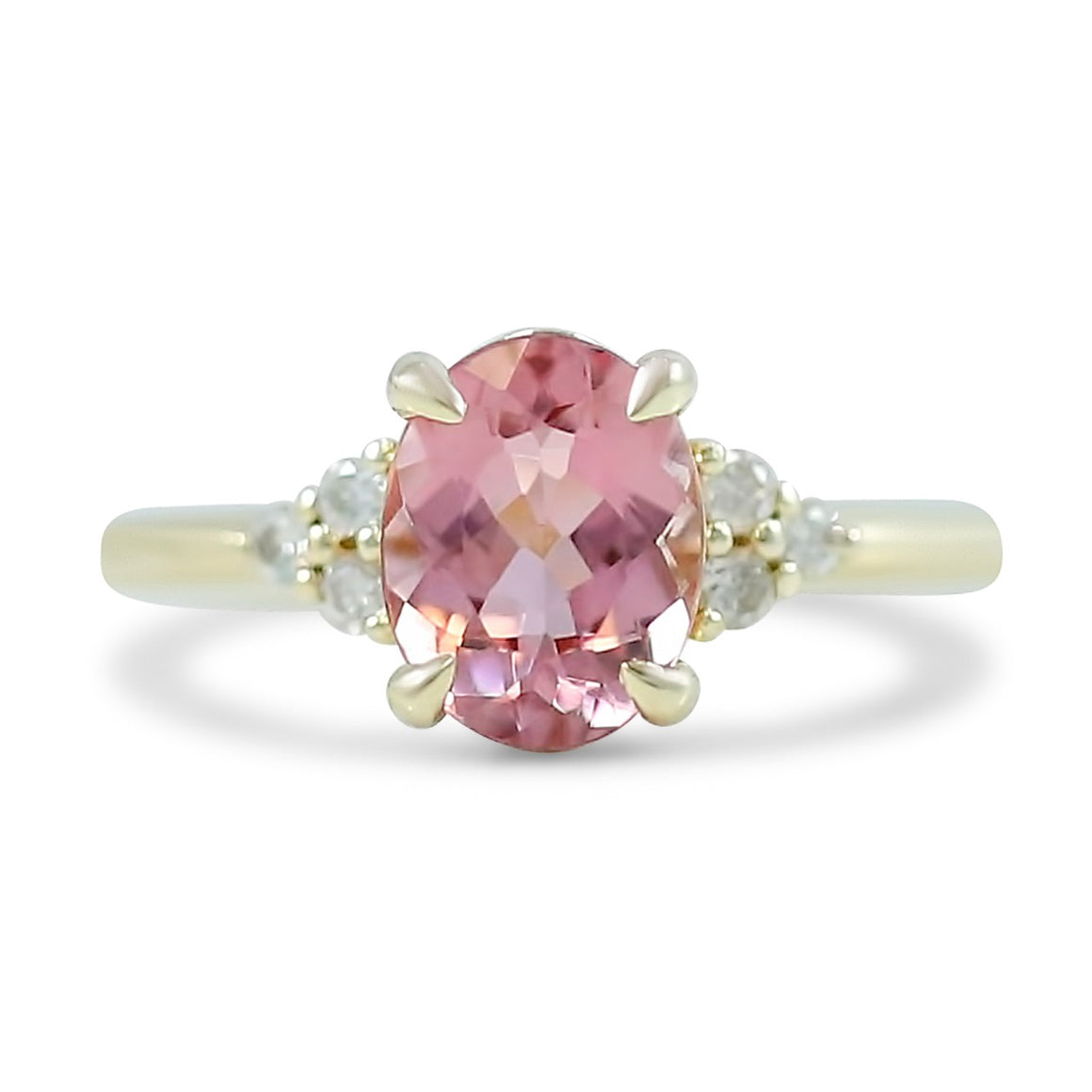 14k yellow gold oval pink tourmaline gemstone engagement ring with clusters of white diamonds on both sides